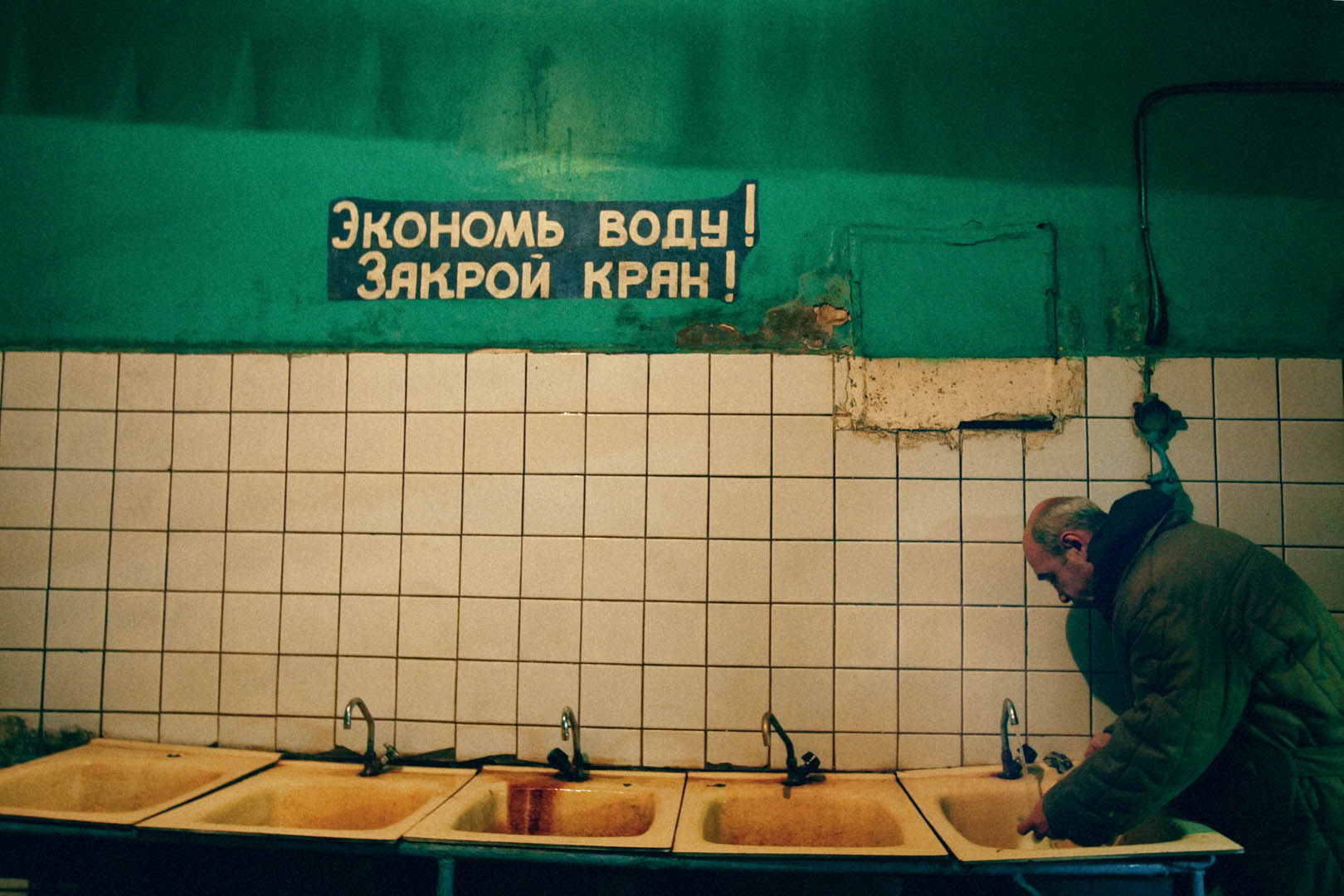 "An inmate washes his hands before dinner, under the sign ""Save the water, close the tap"". Life in LTP is surrounded by signs, instructions, regulations and rules. Labour Treatment Profilactorium for alcohol addicted in Belarus. LTP is a part of the penal system and Belarus is the only country in the world that still practices the punishment of obligatory incarceration for addicts. There are 5 LTP in Belarus, about 1600 inmates each. One LTP is for women, the other ones are only male. The main treatment is labour, and camomile tea."
